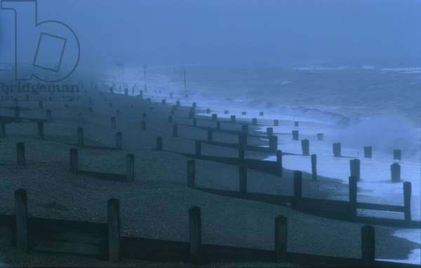 The beach and its breakwaters at dusk in winter with a stormy North Sea, Aldeburgh, Suffolk (photo)