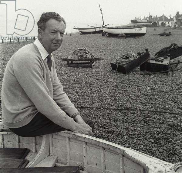 Benjamin Britten sitting on the edge of fisherman's boat, Aldeburgh, Suffolk (b/w photo)