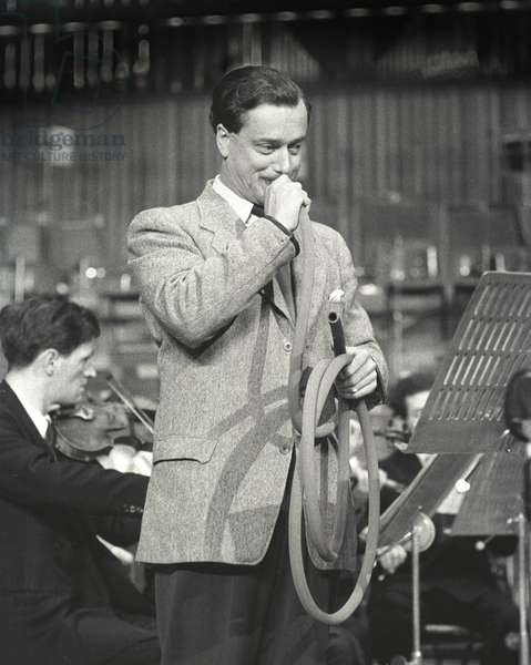 Dennis Brain playing the garden hosepipe, Hoffnung Music Festival at the Royal Festival Hall, London, October 1956 (b/w photo)