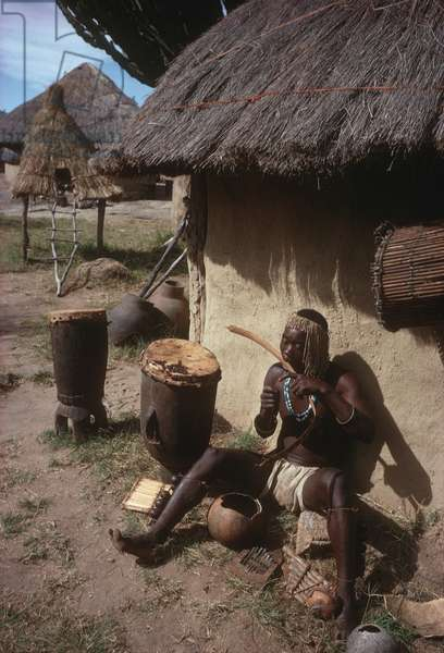 Shona musician plays a wind instrument with drums at his side and background of thatched village buildings, in the village of Mbingura, Zimbabwe (photo)