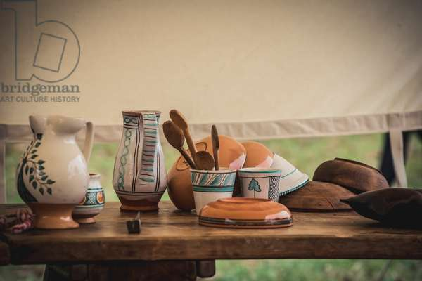 Second half XIV century: Camp: jugs, glasses, cutlery and plates on wooden table, Marimondo, Milan, Italy (photo)
