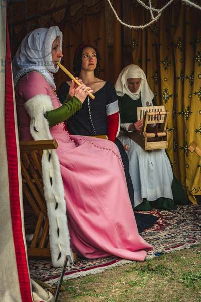 Reconstructive hypotheses of uses and customs, arts and crafts 14th century: Inside a tent, music is made, singing and working on the loom, Villafranca di Verona, Veneto, Italy (photo)