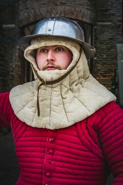 Reconstructive hypothesis of customs and customs, arts and crafts 14th century: Guard at the castle: wearing gambeson and hat of arms, Villafranca di Verona, Veneto, Italy (photo)