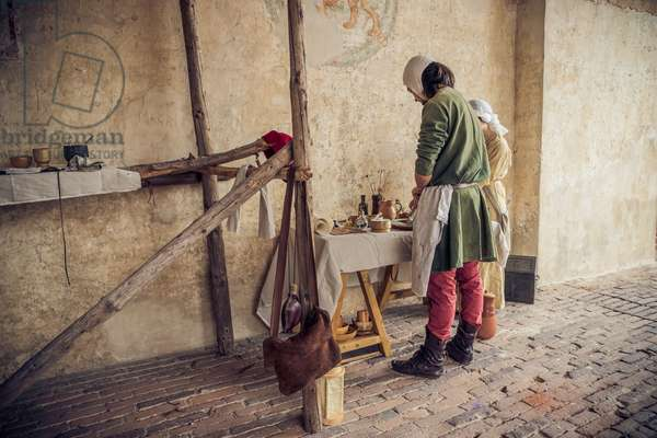 A painter is preparing to fresco a wall of the castle, Middle Ages, Italy XIII century, Hypothesis reconstructive military civilian life inside a castle, Soncino, Lombardy, Italy (photo)