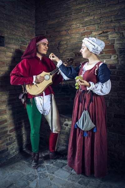 A girl offers a grape grain to the boy who is dedicating a love song to her, Hypothesis reconstructive uses and customs Middle Ages Italy, Mondaino, Italy (photo)