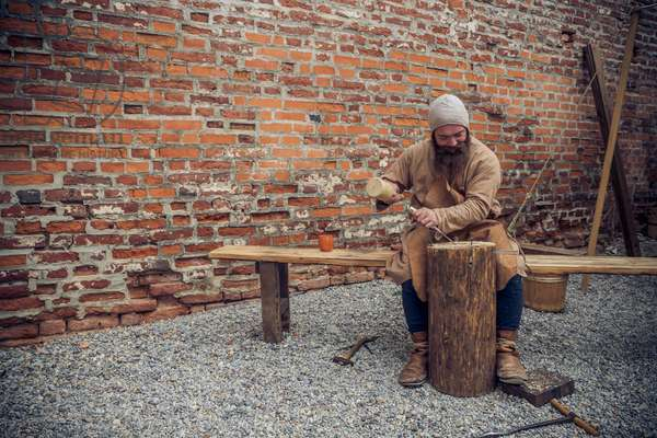 The carpenter carves a log of wood, Middle Ages, Italy XIII century, Hypothesis reconstructive military civilian life inside a castle, Soncino, Lombardy, Italy (photo)