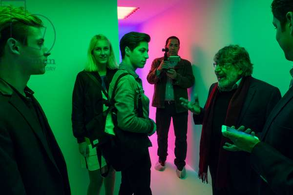 Carlos Cruz-Diez showing the Chromosaturation SCAD to visitors, 2017 (chromatic environment composed of fluorescent tubes with red, green and blue coloured filters)