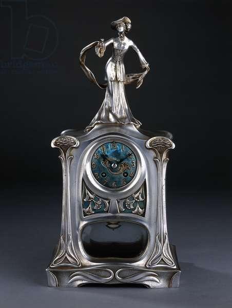 A mantel clock surmounted by a figure of an elegant lady,  (white-metal, blue enamel)