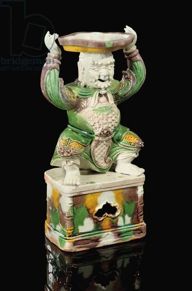 Egg and spinach glazed pricket-stick, modelled as a smiling immortal with scrolling beard, arms raised to support the quatrefoil pricket attachment balanced on his head, Kangxi, 1662-1722 (ceramic)