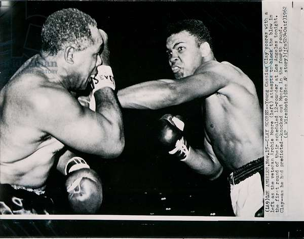 Young Cassius Clay scores with a left against the veteran Archie Moore in the first round of the fight in Los Angeles, 15th November 1962 (b/w photo)