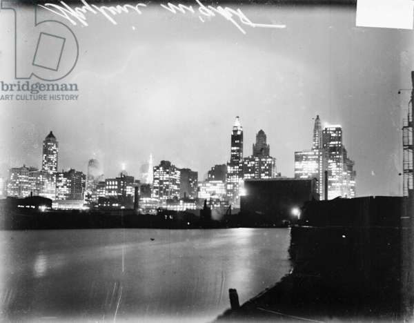 Chicago skyline at night, with light reflecting on Lake Michigan in the foreground, 1929 (b/w photo)