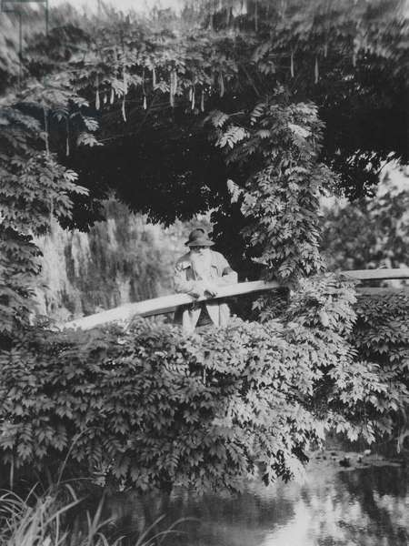 Claude Monet (1841-1926) on the Japanese Bridge in his garden at Giverny, c.1920 (b/w photo)