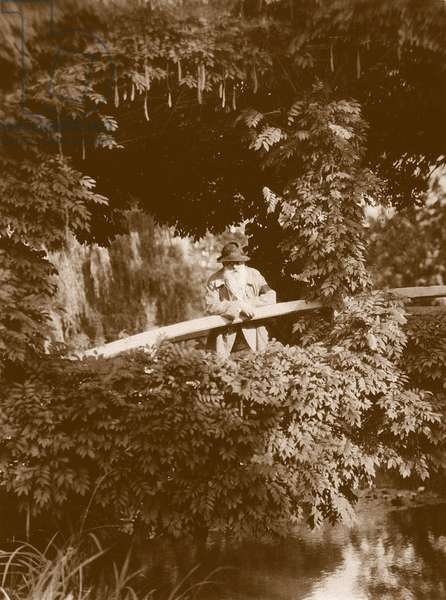 Claude Monet on the Japanese Bridge in his garden at Giverny, c.1920 (b/w photo)