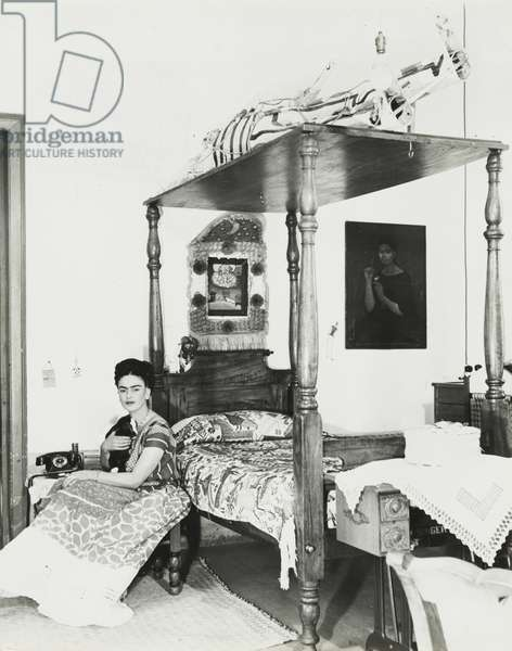 Frida Kahlo in her bedroom with a young goat in her arm, c.1940 (gelatin silver print)
