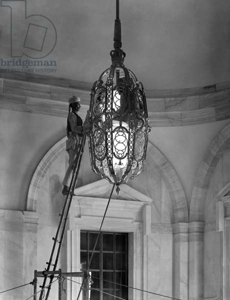 Two members of the 2000-strong Viceroy's House staff clean one of the lamps in the south main staircase, from 'Edwin Lutyens: Country Houses' (b/w photo)