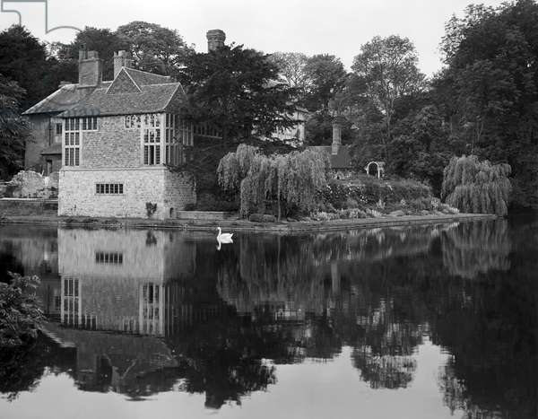 A view of Plumpton Place from over the lake, from 'Edwin Lutyens: Country Houses' (b/w photo)
