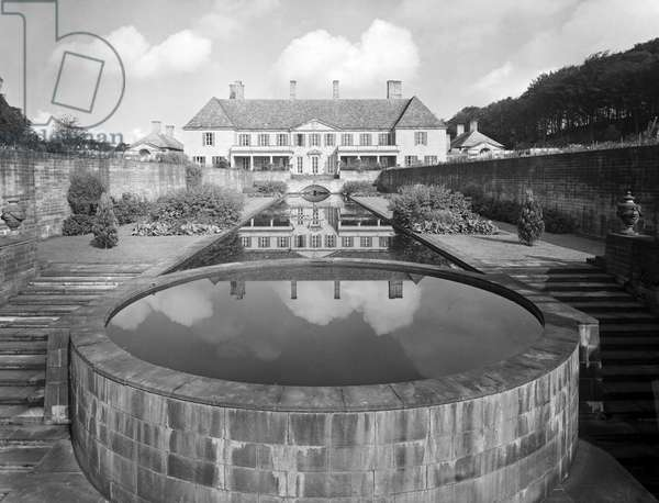 The garden front of Gledstone Hall reflected in the sunk canal, from 'Edwin Lutyens: Country Houses' (b/w photo)