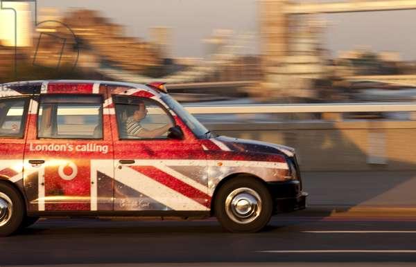 Union Jack taxi driving past Tower Bridge, London, UK (photo)
