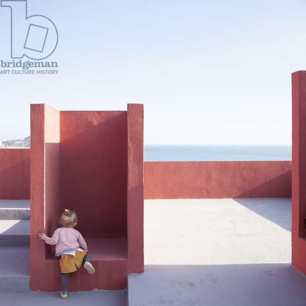 Child exploring La Muralla Roja, designed by architect Ricardo Bofill, Calpe, Alicante, Spain (photo)