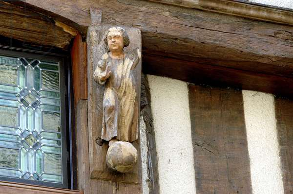 Ancient wooden statue on the walls of a half-timbered house of the 15th century in Walnut sur Serein (Yonne)