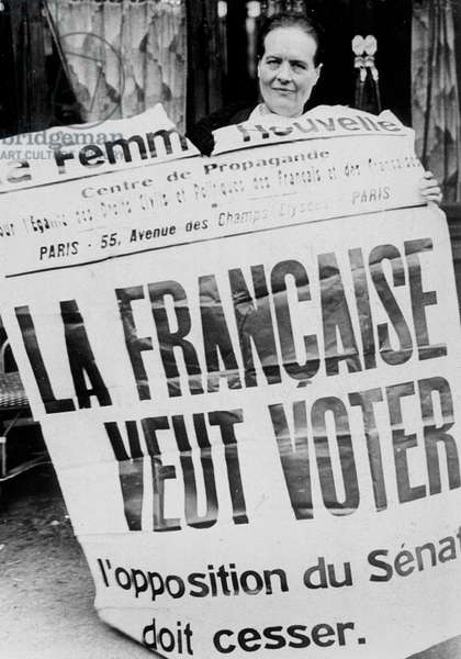 """Louise Weiss brandish a poster for the women 's right to vote published by the revue """" La Femme Nouvelle"""" . She stand in the local elections and prepare her election campaign before the women's vote the 8 th April 1935"""
