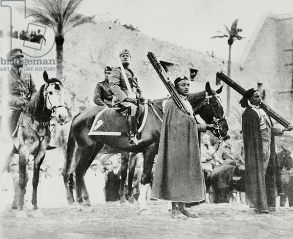 Benito Mussolini on horseback holding the sword of Islam in Tripoli, with Italo Balbo on the left, Libya, from L'Illustrazione Italiana, March 28, 1937