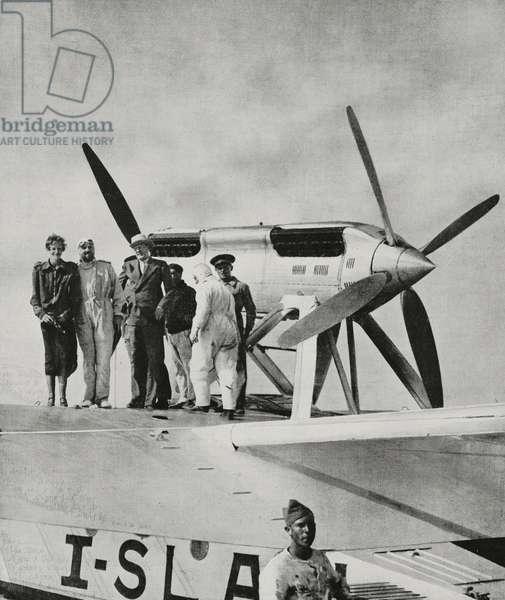 American aviatrix Amelia Earhart (1897-1937), accompanied by Minister of Aeronautics, Italo Balbo (1896-1940), boarding S56 to go to seaplanes school in Orbetello, Rome, Italy, photo by Bruni, from L'illustrazione Italiana, year LIX, n 25, June 19, 1932
