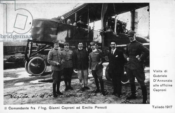 Gabriele D'Annunzio visiting Caproni workshops in Taliedo, Emilio Pensuti on his right, Gianni Caproni on his left and bomber Ca 32 in background, 1917, Italy, World War I, 20th century