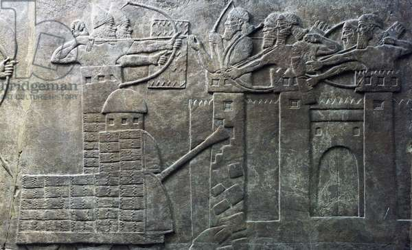 Troops of Assyrian king Ashurbanipal attack city with archers and war machines, relief from palace of Nimrud, Iraq, Assyrian civilization, 7th century BC