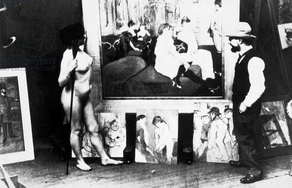 French painter Henri de Toulouse-Lautrec (Albi, 1864-Saint-Andre-du-Bois, 1901) in his studio with a model before his painting Salon in the Rue des Moulins, photograph. Francia, XIX secolo.
