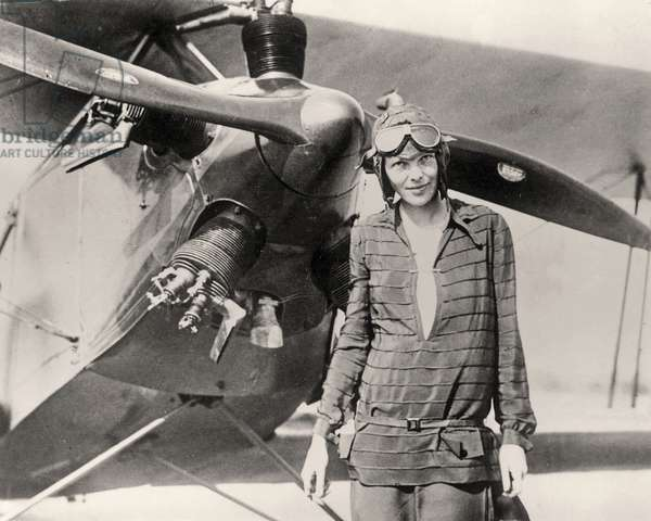 Amelia Earhart in front of her bi-plane called
