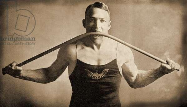 Californian Strongman Mr P. A. Linebarger bends an iron bar with his teeth,San-Francisco c.1922 (photo)