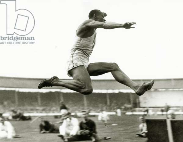 Jesse Owens in action at the long jump during the Berlin Olympics, 1936 (b/w photo)