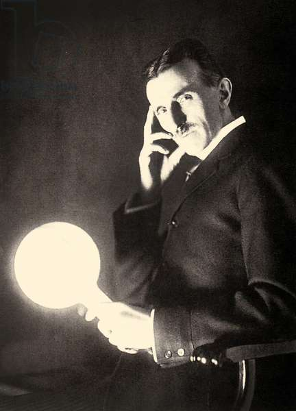 Portrait of Nikola Tesla holding a light bulb illuminated by the electromagnetic field of a Tesla Coil, 1899 (photo)