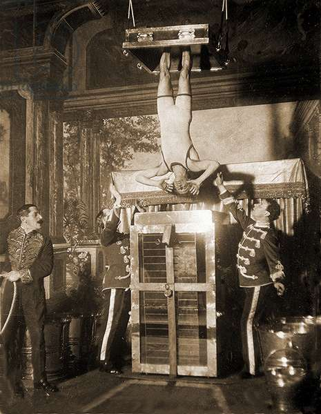 Harry Houdini suspended above a tank of water (sepia photo)