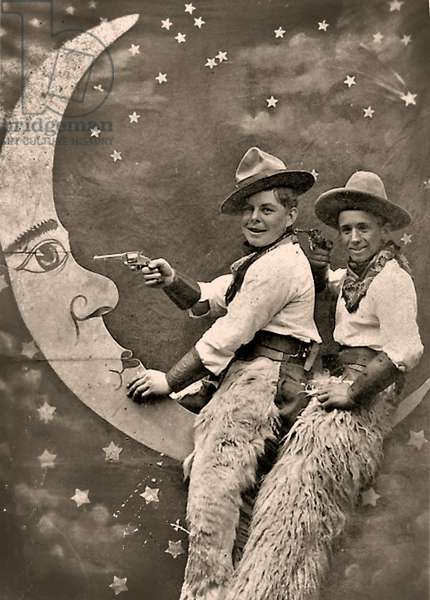 Two boys in Cowboy costumes ride a Paper Moon, 1915 (photo)