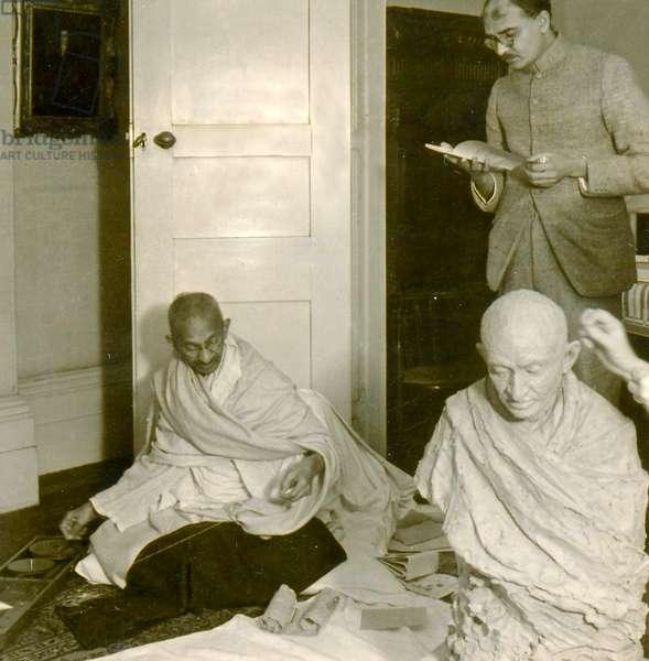 Mohandas Karamchand Gandhi (1869 – 1948) sitting for a sculptor. (photo)