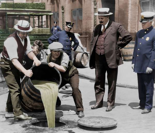New York City Deputy Police Commissioner John A. Leach, right, watching agents pour liquor into sewer following a raid during the height of prohibition, c.1921 (b/w photo)