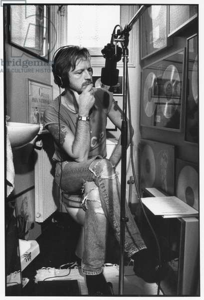 """French singer Renaud (Renaud Sechan) with headphones and microphone, in the toilet, at time of recording of album """"A la belle de mai"""" at home, Paris, 1994 (b/w photo)"""