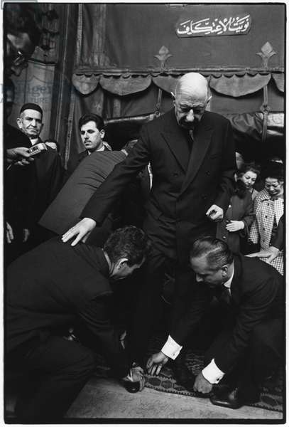 General Charles de Gaulle (1890-1970) putting back his shoes as he comes out of the mosque, Turkey, 28th October 1968 (b/w photo)