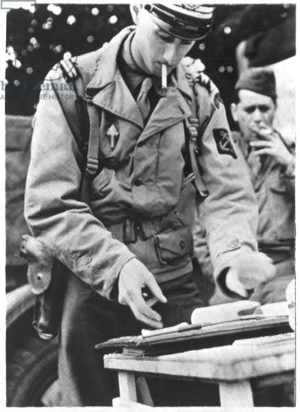Lieutenant Philippe de Gaulle (b.1921) checking a map before going into action in France, 26th August 1944 (b/w photo)