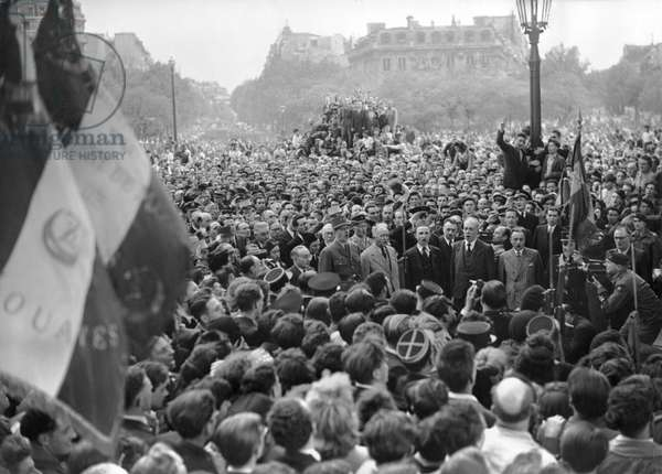 General Charles de Gaulle (1890-1970) starts singing the Marseillaise at the Arc de Triomphe, Place de l'Etoile, among the crowd, 8th May 1945 (b/w photo)