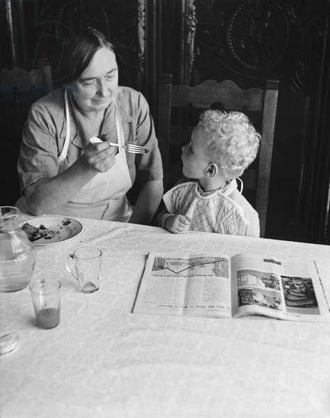 Philomene, cook of General Charles de Gaulle at La Boisserie, feeding Yves de Gaulle, Summer 1954 (b/w photo)