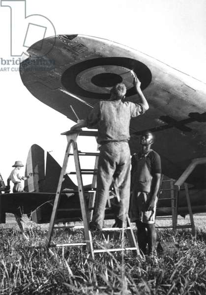 Free France in French Equatorial Africa, a soldier painting the first roundel on an aeroplane wing at Douala, Cameroon, 1940 (b/w photo)