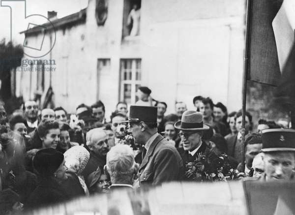 General Charles de Gaulle (1890-1970) shaking hands with Doctor Collon, surrounded by the population of Colombey-les-Deux-Eglises, 21st October 1944 (b/w photo)