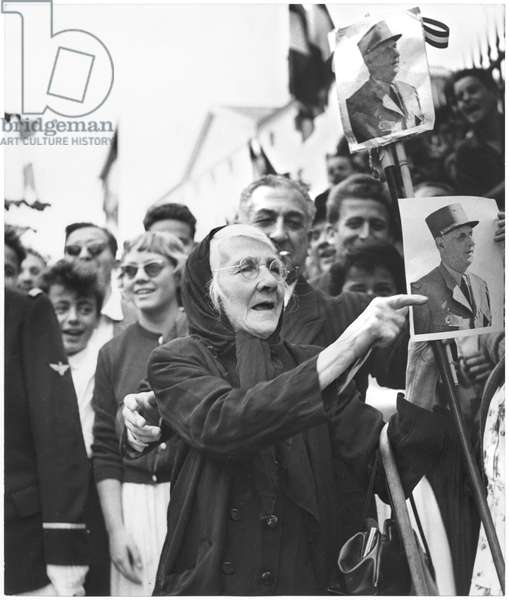 Along the route of Charles de Gaulle (1890-1970) a Corsican woman shows her admiration in holding out a photography of the General, 1958 (b/w photo)