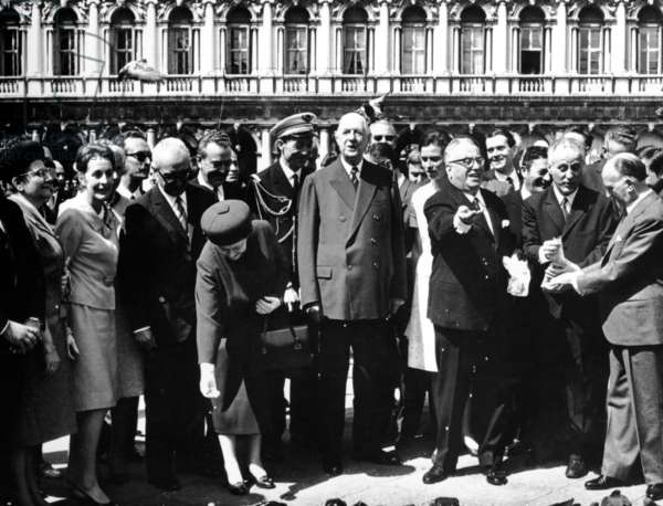 Charles de Gaulle and Yvonne de Gaulle feeding pigeons in St. Mark's Square, with aide de camp Lieutenant Colonel Lurin and Italian President Giuseppe Saragat, Venice, 1 June 1967 (b/w photo)