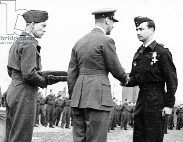 King George VI of England decorating Lieutenant Colonel Gorri, in the presence of Captain MacDonald, Hartfordbridge, England, 14 July 1944 (b/w photo)