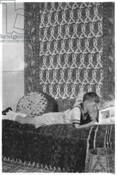 Philippe de Gaulle on the sofa in the study of his father Charles de Gaulle (1890-1970) in their flat rue Tadmore in Beirut, Lebanon, Spring 1931 (b/w photo)