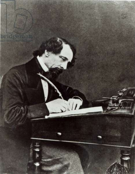 Charles Dickens (1812-70) at his desk, 1858 (b/w photo)